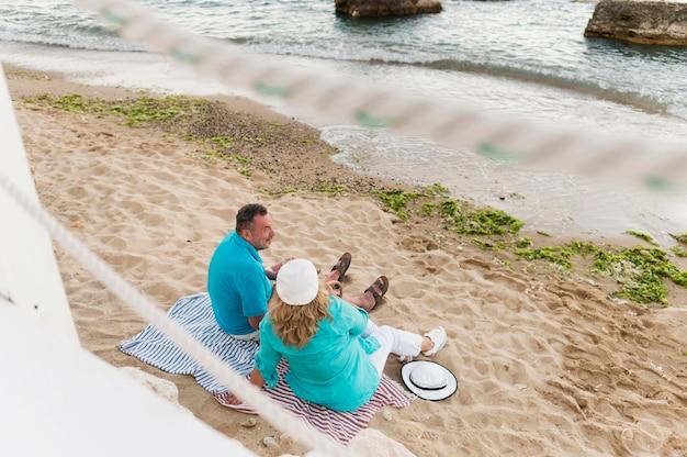 Älteres touristenpaar, das die aussicht am strand genießt