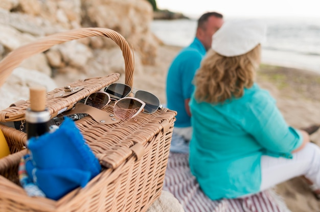 Älteres touristenpaar, das picknick am strand hat