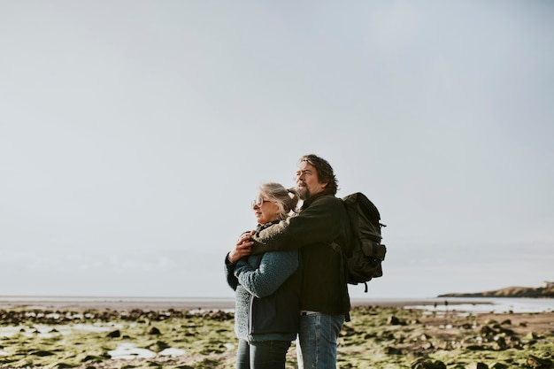Älteres touristenpaar umarmt am strand