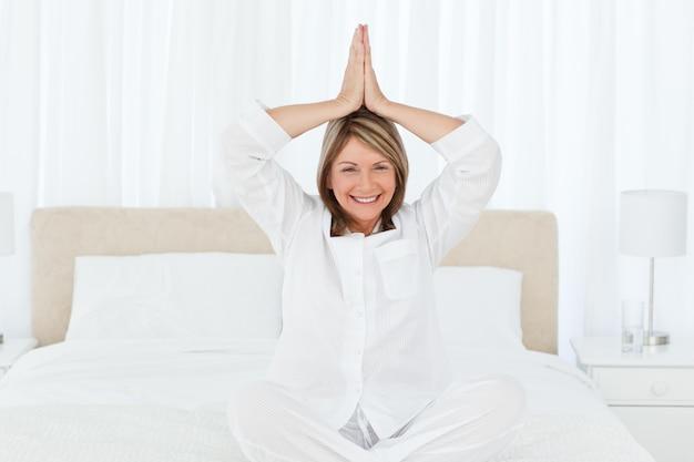 Älteres übendes yoga auf ihrem bett