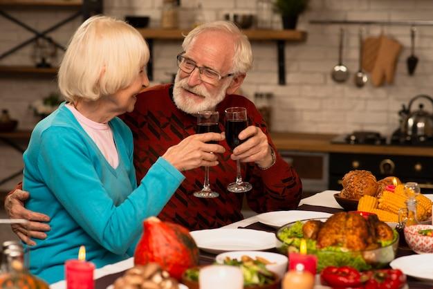 Älteres verheiratetes paar, das gläser röstet und einander betrachtet