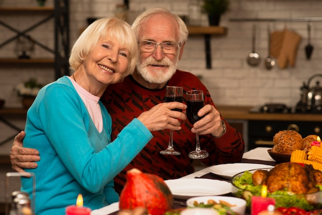 Älteres verheiratetes paar, das gläser röstet und kamera betrachtet