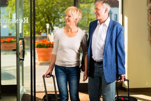 Älteres verheiratetes paar, das im hotel ankommt