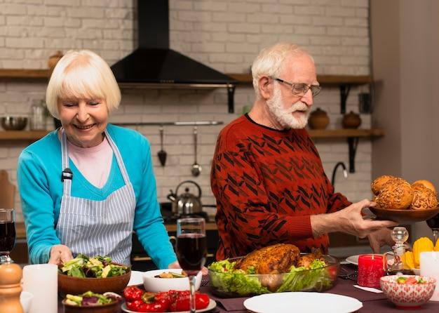 Älteres verheiratetes paar, welches die erntedankmahlzeit vorbereitet