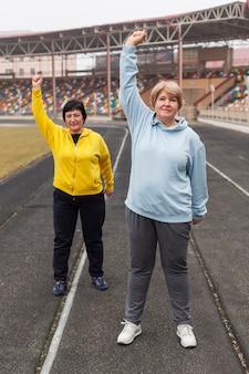 Älteres weibliches paar, das im stadion trainiert