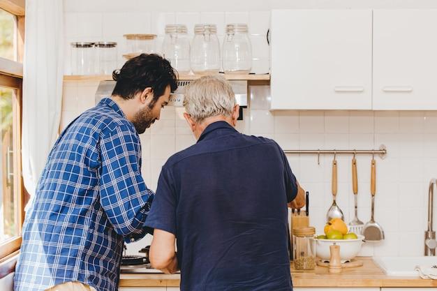 Ältester, der in der küche mit jungem familienvater kocht, um zusammen zu hause zu bleiben.