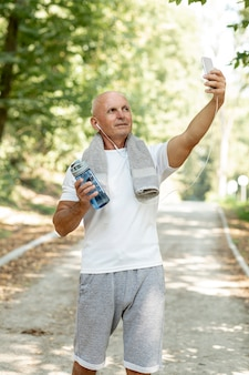 Ältester, der selfie in der sportkleidung mit tuch nimmt