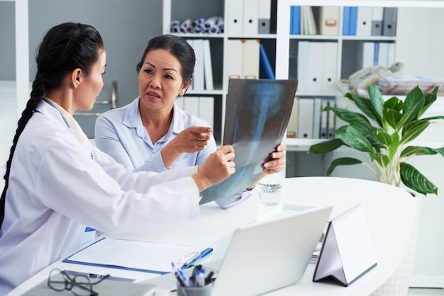 Ängstliche ältere frau, die bei der jährlichen untersuchung mit dem hausarzt über ihre röntgenaufnahme der brust spricht
