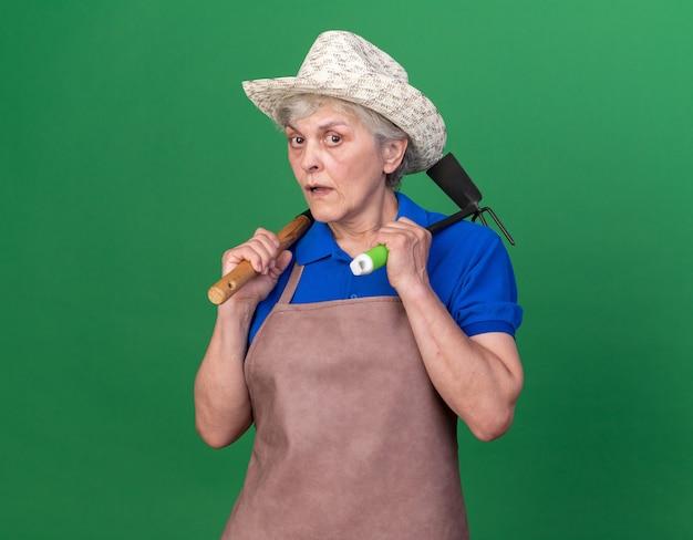 Ängstliche ältere gärtnerin mit gartenhut, die rechen und hacke auf den schultern hält