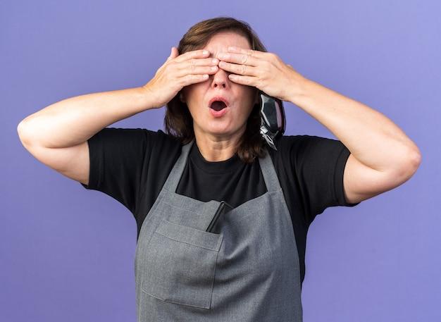 Ängstliche erwachsene friseurin in uniform, die die augen mit den händen bedeckt, die haarschneidemaschine halten, isoliert auf lila wand mit kopierraum