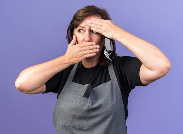 Ängstliche erwachsene friseurin in uniform, die die hand auf die stirn und auf den mund legt, die haarschneidemaschine isoliert auf lila wand mit kopierraum hält