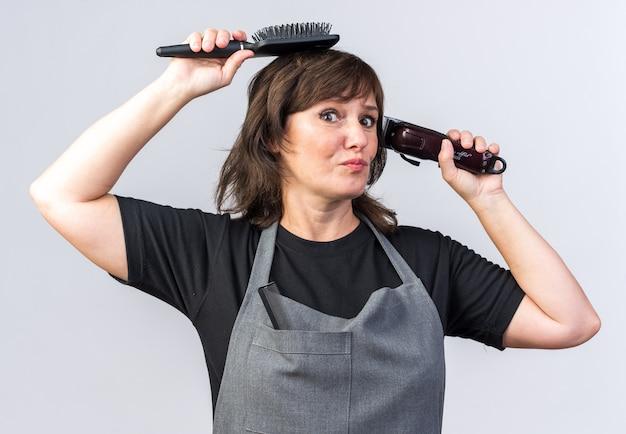 Ängstliche erwachsene friseurin in uniform mit haarschneidemaschine und kamm isoliert auf weißer wand mit kopierraum