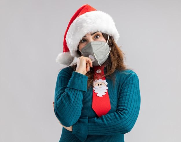Ängstliche erwachsene kaukasische frau mit weihnachtsmütze und weihnachtsmann-krawatte mit medizinischer maske isoliert auf weißer wand mit kopierraum