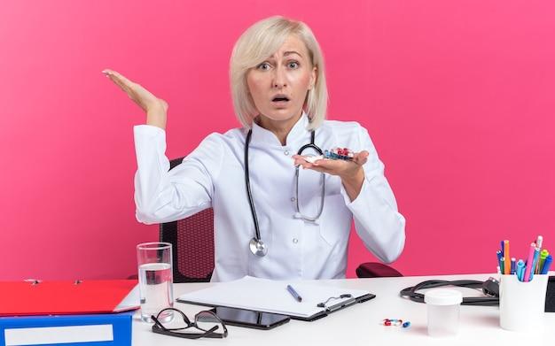 Ängstliche erwachsene slawische ärztin in medizinischer robe mit stethoskop am schreibtisch sitzend mit bürowerkzeugen, die medizintabletten in blisterpackungen einzeln auf rosafarbenem hintergrund mit kopierraum halten holding
