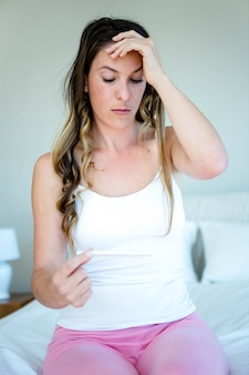 Ängstliche frau, die einen schwangerschaftstest, stehend in ihrem schlafzimmer hält