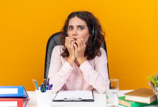 Ängstliche hübsche kaukasische callcenter-betreiberin auf kopfhörern, die am schreibtisch mit bürowerkzeugen sitzen, die sich die hände auf den mund legen