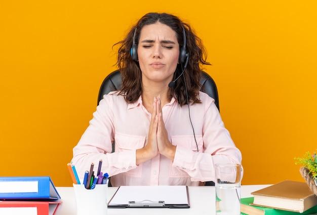 Ängstliche hübsche kaukasische callcenter-betreiberin auf kopfhörern, die mit bürowerkzeugen am schreibtisch sitzen und isoliert auf orangefarbener wand beten