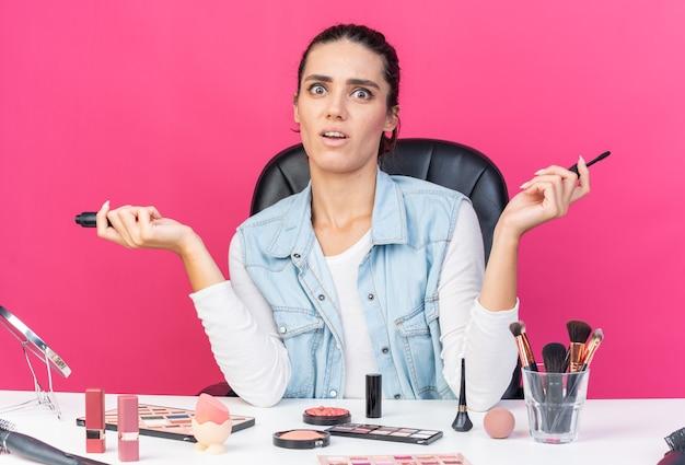 Ängstliche hübsche kaukasische frau, die am tisch mit make-up-tools sitzt und eyeliner hält