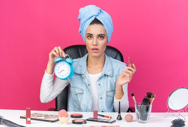 Ängstliche hübsche kaukasische frau mit eingewickeltem haar in handtuch, die am tisch mit make-up-tools sitzt, die lippenstift und wecker einzeln auf rosafarbener wand mit kopienraum hält