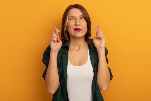 Ängstliche hübsche kaukasische frau steht mit gekreuzten fingern auf orange