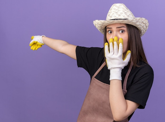 Ängstliche hübsche kaukasische gärtnerin mit gartenhut und handschuhen legt die hand auf den mund und zeigt seitlich isoliert auf lila wand mit kopierraum