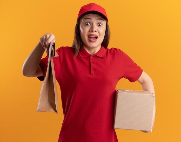 Ängstliche hübsche lieferfrau in uniform hält papierpaket und karton auf orange