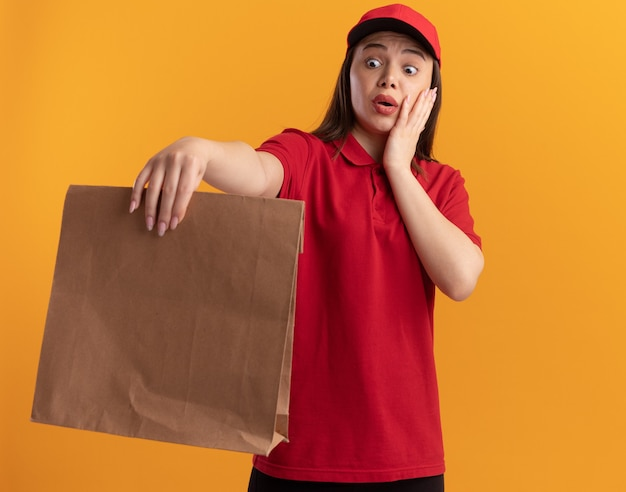 Ängstliche hübsche lieferfrau in uniform legt die hand auf das gesicht, das papierpaket hält und betrachtet