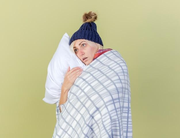Ängstliche junge blonde kranke frau, die wintermütze und schal trägt, die im karierten umarmungskissen eingewickelt betrachten, das seite lokalisiert auf olivgrüner wand betrachtet