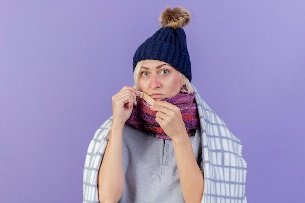 Ängstliche junge blonde kranke slawische frau, die wintermütze und schal trägt