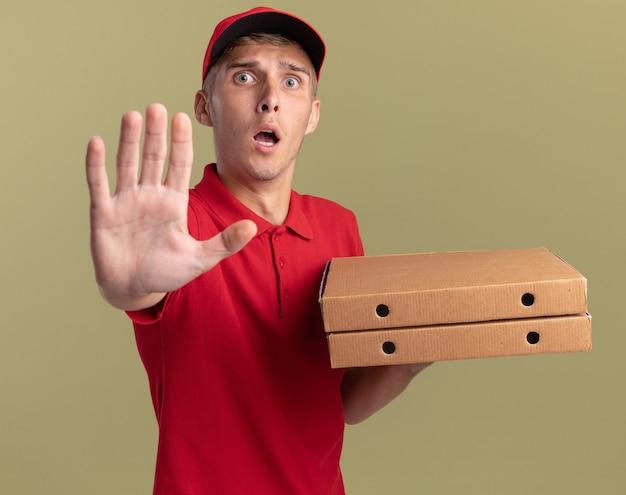 Ängstliche junge blonde lieferjunge hält pizzakartons und gesten stoppschild isoliert auf olivgrüner wand mit kopierraum