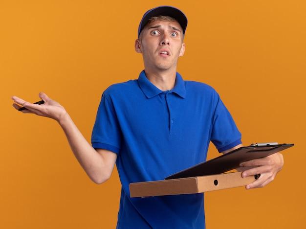 Ängstliche junge blonde lieferjunge hält stift und klemmbrett auf pizzakarton