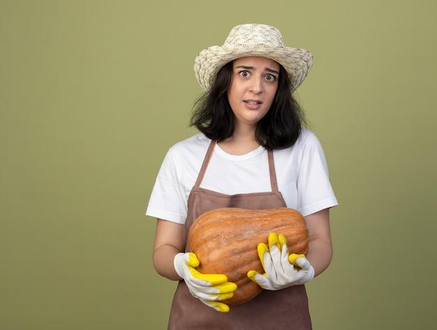 Ängstliche junge brünette gärtnerin in uniform mit gartenhut und handschuhen hält kürbis isoliert auf olivgrüner wand
