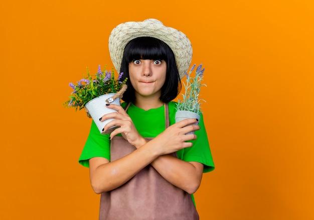 Ängstliche junge gärtnerin in uniform mit gartenhut hält blumentöpfe, die hände kreuzen