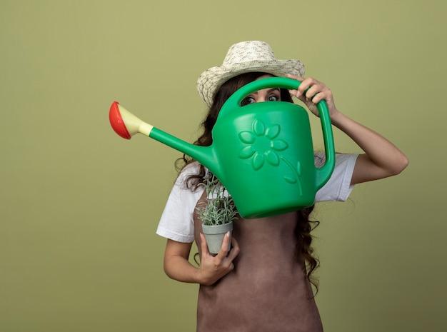 Ängstliche junge gärtnerin in uniform mit gartenhut hält blumentopf und schaut nach vorne durch gießkanne isoliert auf olivgrüne wand