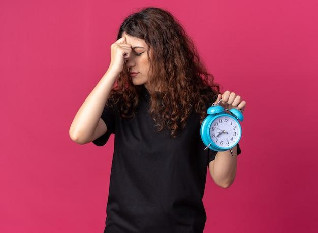 Ängstliche junge hübsche frau, die die hand auf dem kopf hält und den wecker mit geschlossenen augen hält, isoliert an der purpurroten wand