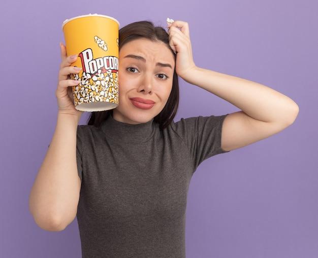 Ängstliche junge hübsche frau, die einen eimer popcorn und ein popcornstück hält, das den kopf mit dem eimer popcorn und der hand berührt, die vorne isoliert auf lila wand schaut