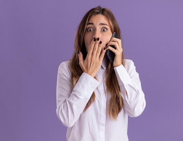 Ängstliche junge hübsche kaukasische mädchen legt die hand auf den mund und telefoniert isoliert auf lila wand mit kopierraum