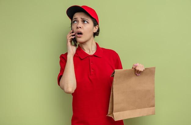 Ängstliche junge hübsche lieferfrau, die am telefon spricht und eine papiertüte hält, die auf die seite schaut