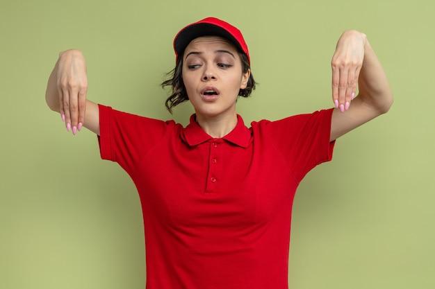 Ängstliche junge hübsche lieferfrau, die mit erhobenen händen steht und nach unten schaut