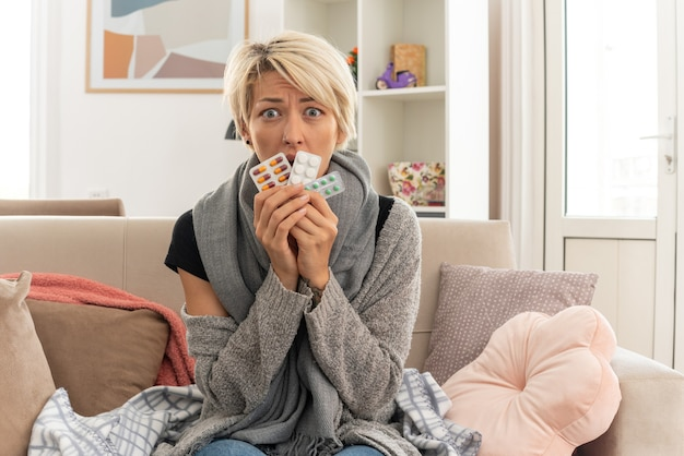 Ängstliche junge kranke slawische frau mit schal um den hals, die medizinblisterpackungen auf der couch im wohnzimmer hält