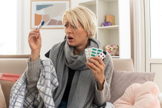 Ängstliche junge kranke slawische frau mit schal um den hals, eingewickelt in plaid, die medizinblisterpackungen hält und auf das thermometer schaut, das auf der couch im wohnzimmer sitzt