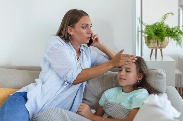 Ängstliche junge mutter ruft krankenwagenarzt an, kümmert sich um kranke kleine mädchen mit grippe und hoher temperatur. besorgte mutter kontakttherapeut oder kinderarzt mit kleiner tochter fühlen sich krank.