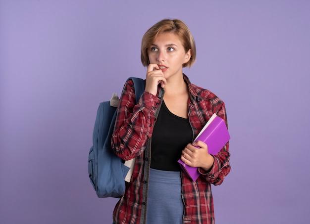 Ängstliche junge slawische studentin mit rucksack beißt nagel hält buch und notizbuch