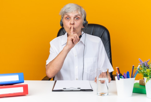 Ängstliche kaukasische callcenter-betreiberin auf kopfhörern, die am schreibtisch mit bürowerkzeugen sitzen und stillegeste einzeln auf orangefarbener wand ausführen