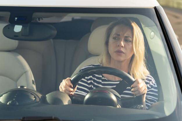 Ängstliche verängstigte fahrerin besorgt, die einen autounfall auf der straße durch das windschutzscheiben-antriebsfahrzeug betrachtet