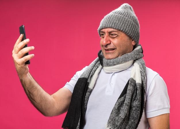 Ängstlicher erwachsener kranker kaukasischer mann mit schal um den hals, der eine wintermütze trägt und das telefon isoliert auf rosa wand mit kopienraum betrachtet