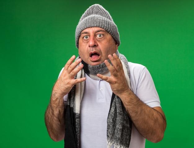 Ängstlicher erwachsener kranker kaukasischer mann mit schal um den hals mit wintermütze, der die hände offen hält, isoliert auf grüner wand mit kopierraum