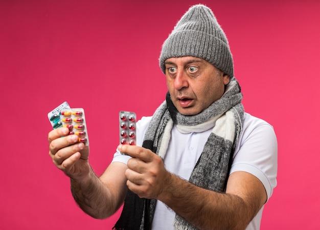 Ängstlicher erwachsener kranker kaukasischer mann mit schal um hals, der wintermütze hält und verschiedene medizinpackungen isoliert auf rosa wand mit kopienraum betrachtet