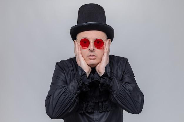 Ängstlicher erwachsener mann mit hut und sonnenbrille in schwarzem gothic-hemd, der hände auf sein gesicht legt und schaut