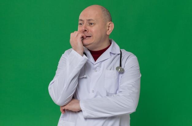 Ängstlicher erwachsener slawischer mann in arztuniform mit stethoskop, das sich die nägel beißt und auf die seite schaut